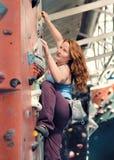 红头发人妇女室内攀岩 坚强的女性登山人 图库摄影