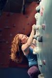 红头发人妇女室内攀岩 坚强的英勇女性登山人 免版税库存图片