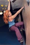 红头发人妇女室内攀岩 强的女性活跃生活方式 库存照片