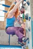 红头发人妇女攀岩 女性攀岩运动员室内墙壁 免版税库存图片