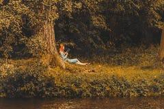 年轻红头发人妇女阅读书在秋天公园 库存照片