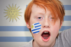 红头发人有在他的面孔绘的乌拉圭旗子的爱好者男孩 免版税库存图片