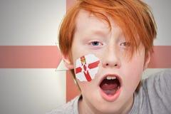 红头发人有在他的面孔绘的北爱尔兰旗子的爱好者男孩 免版税图库摄影