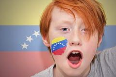 红头发人有在他的面孔绘的委内瑞拉旗子的爱好者男孩 库存图片