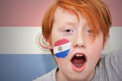 红头发人有在他的面孔绘的巴拉圭旗子的爱好者男孩 库存图片