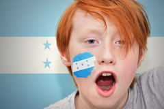 红头发人有在他的面孔绘的洪都拉斯旗子的爱好者男孩 库存照片