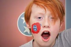 红头发人有田纳西在他的面孔绘的状态旗子的爱好者男孩 免版税库存图片