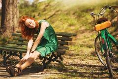 红头发妇女安装与减速火箭的自行车 库存照片