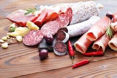 纤巧jamon和被急拉的香肠fuet肉盛肉盘在一张木桌上 免版税图库摄影