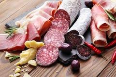 纤巧jamon和被急拉的香肠fuet肉盛肉盘在一张木桌上 免版税库存图片