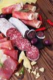 纤巧jamon和被急拉的香肠fuet肉盛肉盘在一张木桌上 免版税库存照片