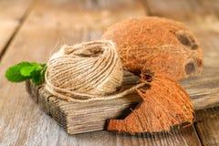 纤维在一张老木桌上的粗硬纤维和椰子壳绳索  库存照片