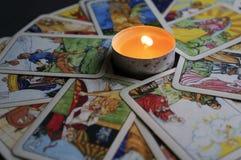 约什卡尔奥拉,俄罗斯- 2017年11月13日:在占卜用的纸牌的算命在与一个灼烧的蜡烛的黑背景 库存图片