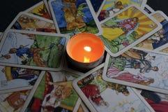 约什卡尔奥拉,俄罗斯- 2017年11月13日:在占卜用的纸牌的算命在与一个灼烧的蜡烛的黑背景 免版税库存照片