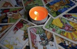 约什卡尔奥拉,俄罗斯- 2017年11月13日:在占卜用的纸牌的算命在与一个灼烧的蜡烛的黑背景 免版税库存图片