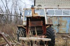 约什卡尔奥拉,俄罗斯- 2017年11月23日:有一个运转的引擎的一台老被放弃的生锈的拖拉机 免版税库存图片