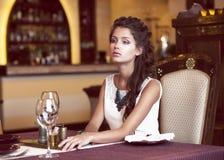 约会。 作等待在餐馆内部的装饰的表的妇女 免版税库存照片
