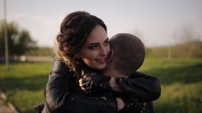 约会人和女孩皮夹克的坐摩托车亲吻反对高速公路的背景 影视素材