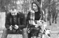 约会在一条长凳的公园恋人在雪 图库摄影