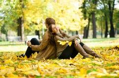 约会在黄色叶子的夫妇 免版税库存照片