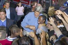 约翰・克里参议员拥抱非裔美国人的孩子在托马斯Mack中心在UNLV,拉斯维加斯, NV 免版税库存图片