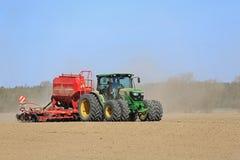 约翰Deere在多灰尘的领域的拖拉机和条播机 免版税库存图片