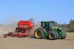 约翰Deere在春天领域的拖拉机和条播机 图库摄影