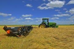 约翰Deere拖拉机和swather在麦田 免版税图库摄影