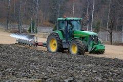 约翰Deere 8100农业拖拉机和Kverneland PB100耕犁 库存图片
