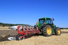 约翰Deere 6630拖拉机和犁领域的Agrolux犁 库存图片