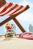 纪念品圣诞老人在deckchair下的雪地球在海滩关闭 库存图片