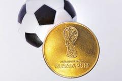 纪念硬币致力2018年世界杯 在背景中是足球 库存图片
