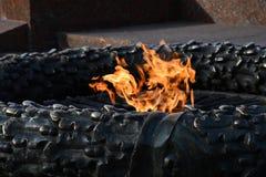 纪念碑永恒火焰燃烧的火特写镜头在傲德萨乌克兰的市公园 在铜雕塑里面的明亮的橙色火焰 免版税库存图片