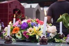 纪念蜡烛和花在坟墓 库存照片