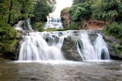 纯净和冷的山河跑在岩石石头之间并且流动入瀑布 免版税图库摄影