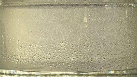 纯净的水或酒精滴水下落在一个玻璃瓶子里面的,在银色背景 蒸馏过程 特写镜头 股票录像