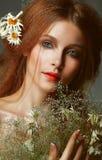 纯净的秀丽。拿着野花的花束赤褐色女孩。柔软 免版税库存照片