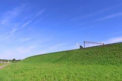 纯净的蓝天、鲜绿色的草坪和路在小山 库存照片