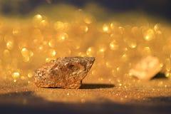纯净的金矿物的关闭与在黑背景、投资和企业概念的金黄光 库存图片
