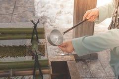 纯净身体和心脏的日本水浸染工在对是的日本寺庙的步行前相信日本宗教 免版税库存照片