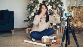 纯熟女孩创造性的vlogger记录关于礼物盒的录影和在装饰的圣诞节附近提出包裹开会 影视素材