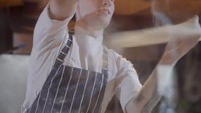 纯熟正面比萨制造者虚构面团在现代餐馆厨房关闭 厨师制服的年轻微笑的人 股票录像