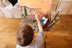 纯熟男孩有绘画教训在学校 库存图片