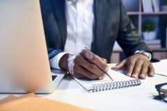 纯熟雇员采取在他的日志的有些笔记 免版税库存图片