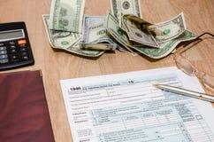 纳税申报1040文件与计算器和美元的2016年 图库摄影