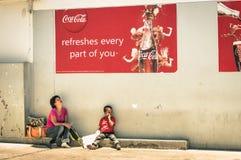 纳米比亚母亲和儿子在可口可乐广告牌下 库存照片