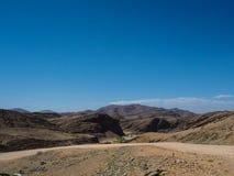 纳米比亚沙漠独特的地理巨大岩石山纹理衬里风景与分裂的石地面路和沙漠植物的 图库摄影