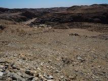 纳米比亚沙漠独特的地理概略的岩石山纹理风景背景与分裂的石地面和沙漠植物的 库存图片