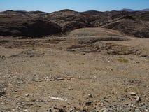 纳米比亚沙漠独特的地理美好的岩石山纹理风景背景与分裂的石地面和沙漠植物的 库存照片