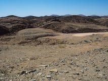 纳米比亚沙漠独特的地理自然岩石山纹理风景背景与分裂的石含沙地面的 免版税库存照片